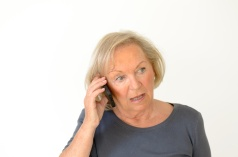 Seniorin im Freizeitlook telefoniert mit Smartphone